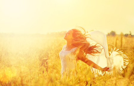 Teenage model girl in white dress running on the spring field