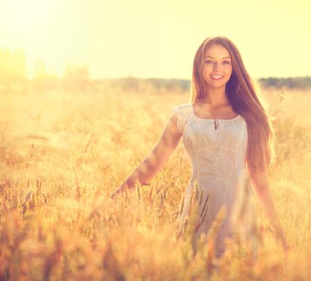 Mooie tiener model meisje in witte jurk lopen op het veld Stockfoto
