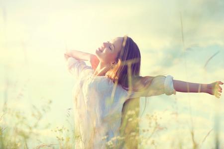 Chica modelo adolescente en el vestido blanco que se divierte en el campo de verano Foto de archivo