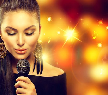 singing: Singing Woman with Microphone over Blinking Background Stock Photo