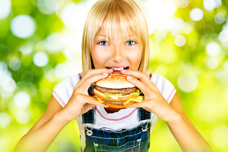 Pretty little girl eating a hamburger over nature background photo