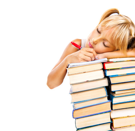 Tired schoolgirl sleeping on stack of books  Education concept  photo