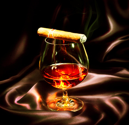 Cognac and cigar  Glass of brandy over dark background
