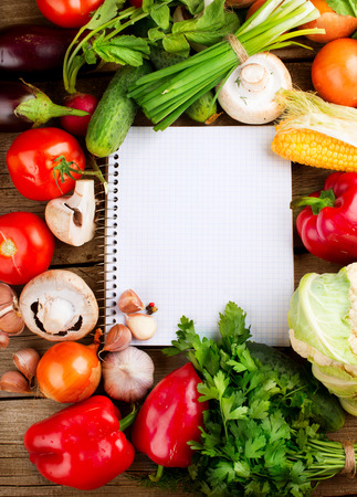 Fresh Vegetables on a Wooden Background and Paper for Notes photo