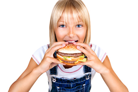 Pretty little girl eating a hamburger isolated on white photo