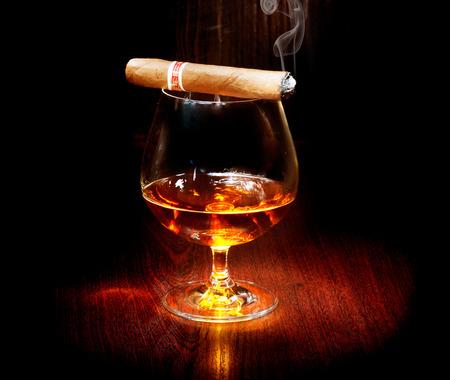 cigarro: Coñac y cigarros Copa de brandy sobre fondo oscuro