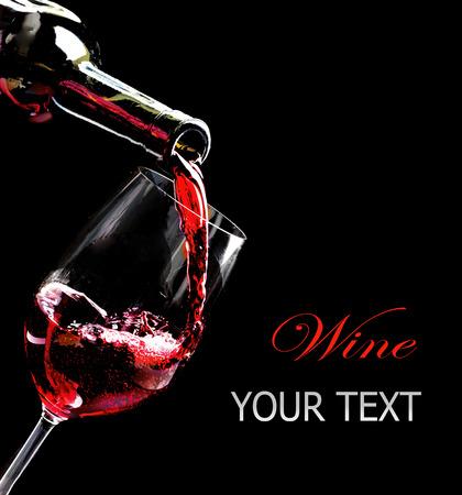 wine pouring: Vino rosso versando in un bicchiere da bottiglia isolato su nero Archivio Fotografico