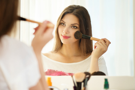 makeup: Beauty woman looking in the mirror and applying makeup Stock Photo