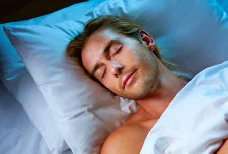lifestyle: Young Man Sleeping w jego łóżku
