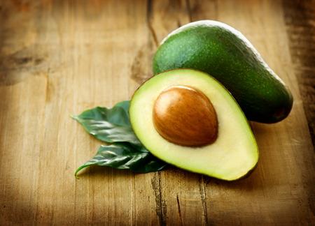 avocado: Avocado Avocado Biologico con foglie su un tavolo di legno Archivio Fotografico