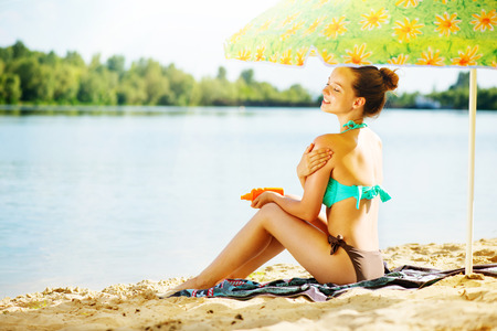 Beautiful girl applying sun tan cream on her skin on the beach Stock Photo