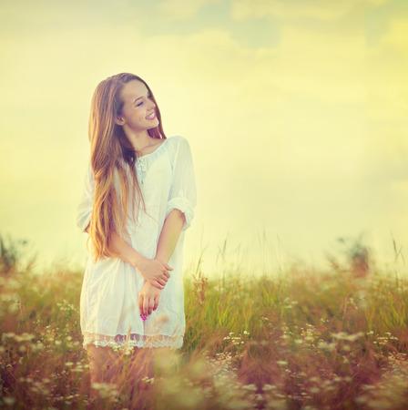 自然を楽しんでいる白いドレスで美しい十代のモデルの女の子