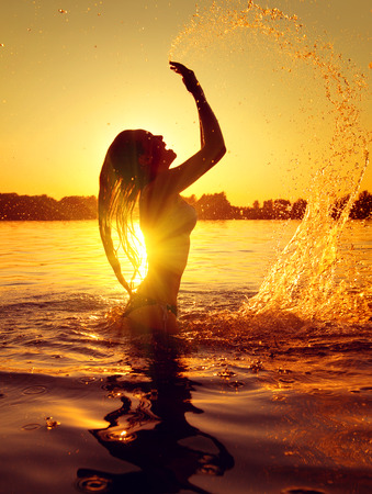 Teen girl swimming and splashing on summer beach over sunset photo