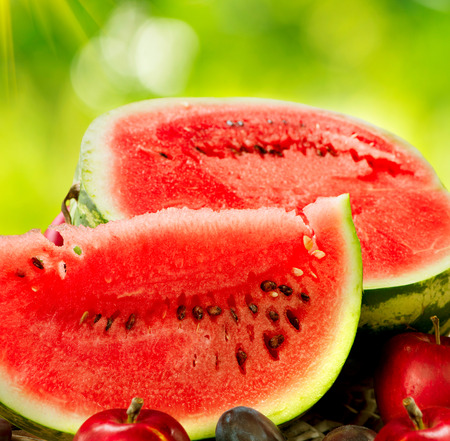 Juicy ripe organic watermelon closeup over nature background photo