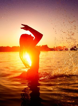 petite fille maillot de bain: Natation adolescente et les �claboussures sur la plage d'�t� sur le coucher du soleil