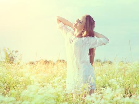 Menina modelo adolescente bonita no vestido branco que aprecia a natureza