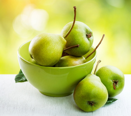 Ripe organic pears over nature green blurred background photo
