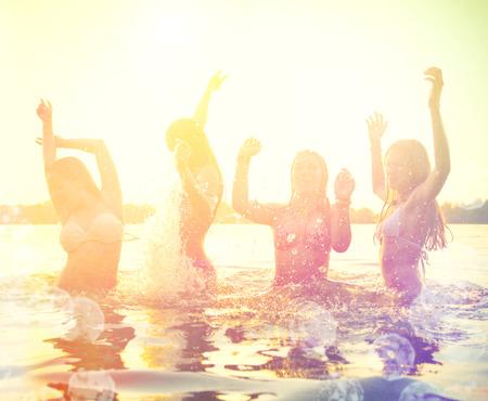 playa: Grupo de niñas adolescentes felices jugando en la playa en la puesta del sol
