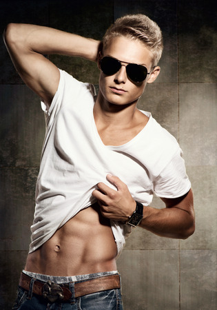Handsome young man  Cheerful sexy guy wearing sunglasses photo