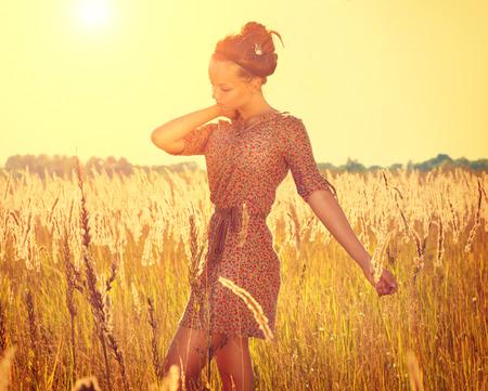 Beautiful teenage girl in short dress posing on the field photo