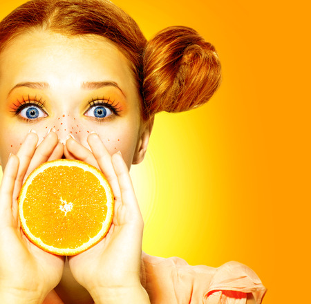 Girl takes juicy orange  Beauty joyful teen girl with freckles