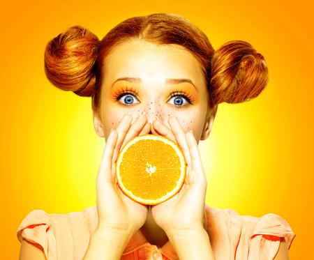 jugos: La muchacha toma Belleza jugosa naranja chica alegre adolescente con pecas Foto de archivo