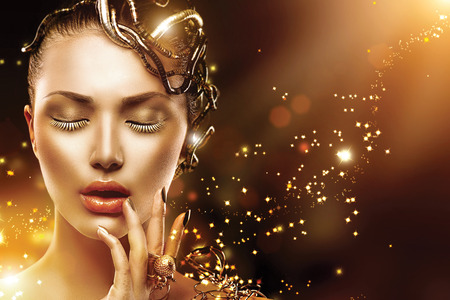 Model woman face with gold skin, nails, make-up and accessories