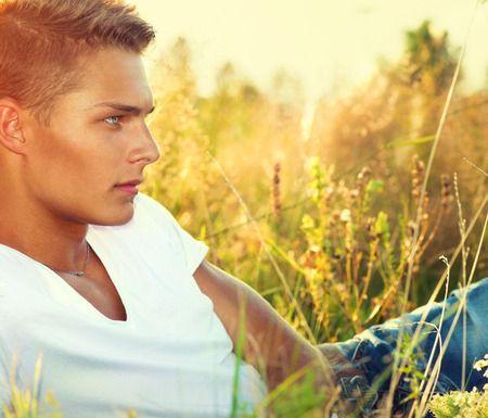 seducer: Handsome guy lying on the field. Young man enjoying nature