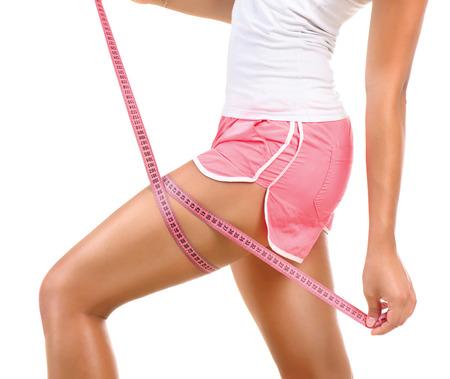 Sportig modell flicka mäter hennes ben med ett måttband