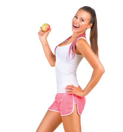 salud y deporte: Deportivo chica que sostiene una manzana mientras est� de pie hacia los lados Foto de archivo
