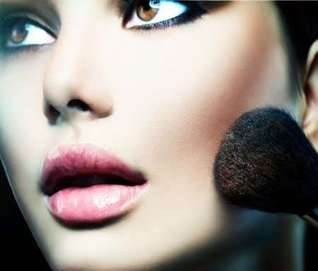 make-up poeder: Make-up aanbrengen. Mooie mannequin meisje gezicht close-up Stockfoto