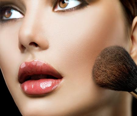 make up applying: Makeup applying. Beautiful fashion model girl face closeup