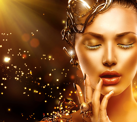 Model woman face with gold skin, nails, make-up and accessories photo
