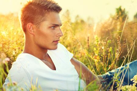 modelos masculinos: Chico guapo acostado en el campo. Hombre joven disfrutar de la naturaleza Foto de archivo