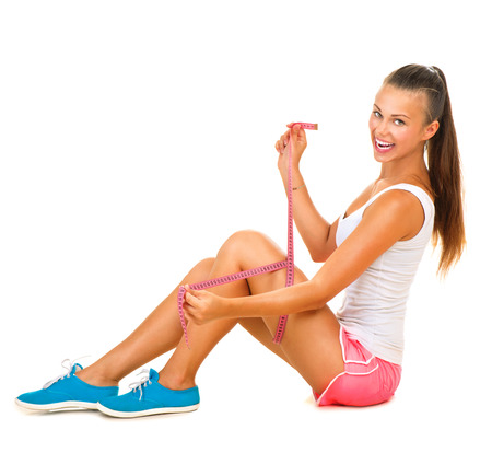 Sporty model girl measures her leg with a measuring tape Standard-Bild