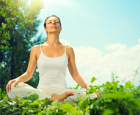 people   lifestyle: Young woman doing yoga exercises outdoors Stock Photo