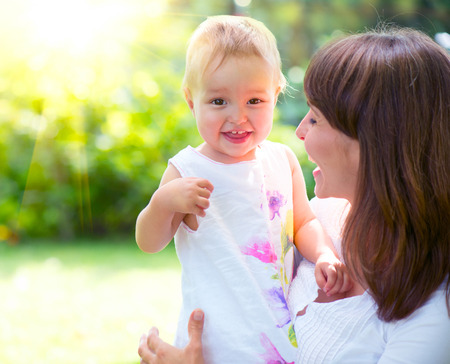 Beautiful mother and baby playing in a park photo