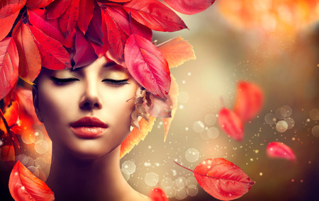 Autumn Woman. Fall. Girl with colourful autumn leaves hairstyle 스톡 콘텐츠