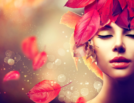 falls: Autumn Woman. Fall. Girl with colourful autumn leaves hairstyle Stock Photo
