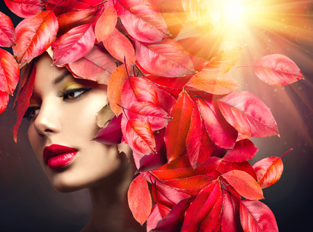 Autumn Woman. Fall. Girl with colourful autumn leaves hairstyle Standard-Bild