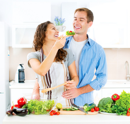 alimentacion sana: Pareja felices que cocinan junto. Ensalada de verduras. Hacer dieta Foto de archivo