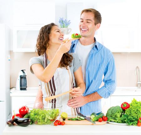 Pares felizes que cozinham juntos. Salada de legumes. Dieta Banco de Imagens