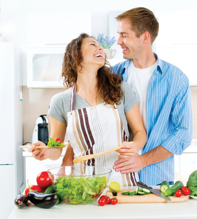 Man and Woman in their Kitchen Preparing Vegetable Salad photo