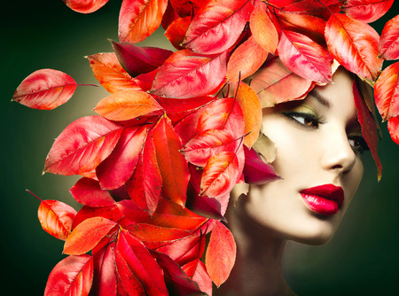 Autumn Woman. Fall. Girl with colourful autumn leaves hairstyle Archivio Fotografico