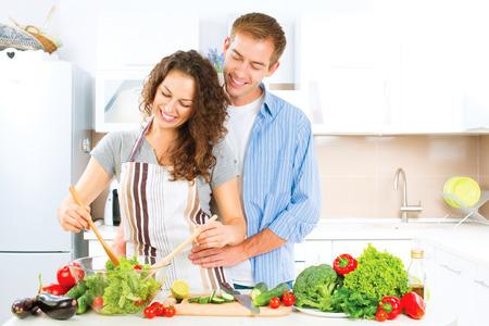animados: Pareja felices que cocinan junto. Ensalada de verduras. Hacer dieta Foto de archivo