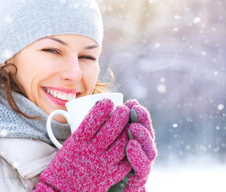 屋外の温かい飲み物を含む美しい幸せな笑みを浮かべて冬女