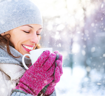 winter forest: Beautiful happy smiling winter woman with hot drink outdoor