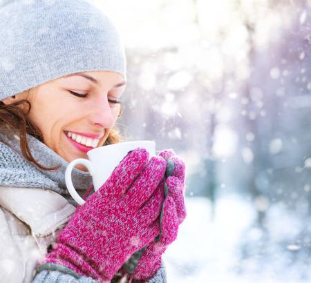 sapin neige: Belle sourire heureux femme d'hiver avec boisson chaude en plein air