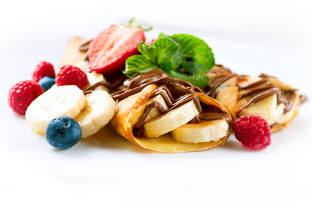 продукты питания: Блинчики с бананом, шоколадом и ягодами крупным планом