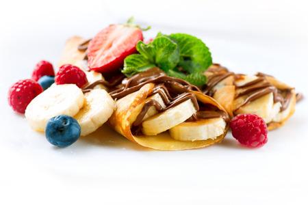 postres: Crepes con pl�tano, chocolate y bayas de cerca Foto de archivo